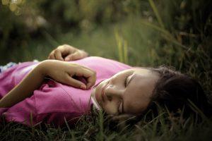 vrouw met roze shirt die in het gras ligt