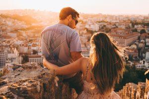 man en vrouw die samen op een rots zitten en boven een stad uitkijken