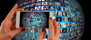 mens houdt telefoon voor een wereldbol met gezichten van heel veel verschillende mensen