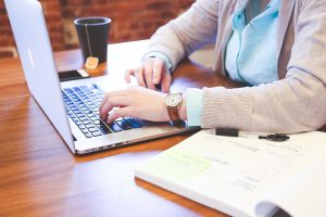 vrouw die op een macbook laptop bezig is